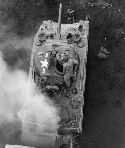 An M4 Sherman wading tank is seen mired in the mud on a a Normandy invasion beach