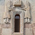 Stone carving of Armenian bearded priests raising church above window
