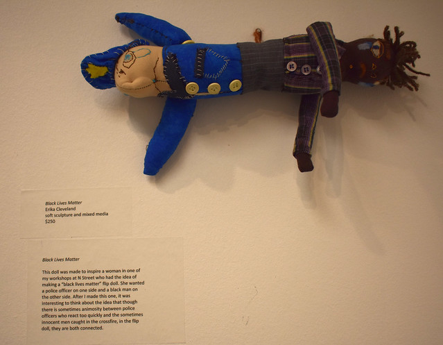 Photo of a flip doll made to represent a police officer and a person of color, titled