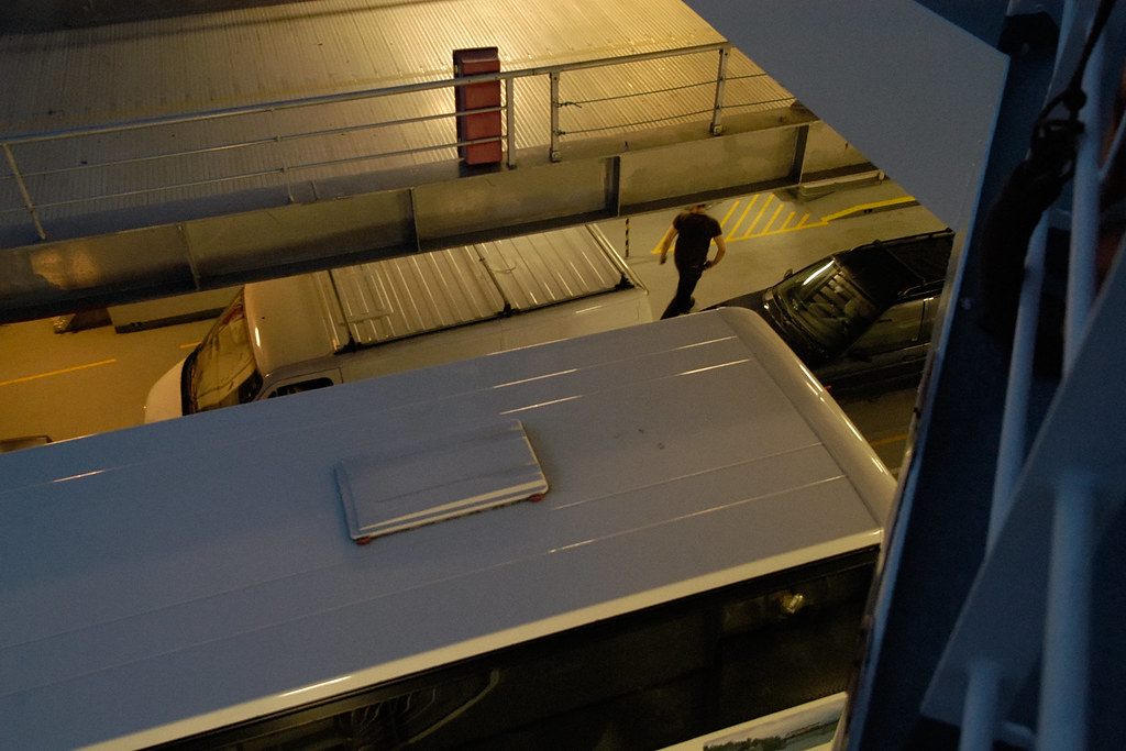 White bus roof on a car ferry, man walking past car.