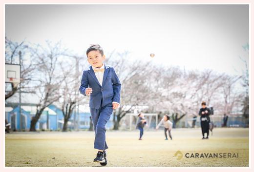 小学校入学記念 スーツを着て運動場を走る男の子