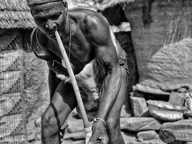 Fotografía en blanco y negro de un hechicero taneka encendiendo su pipa (Benín)