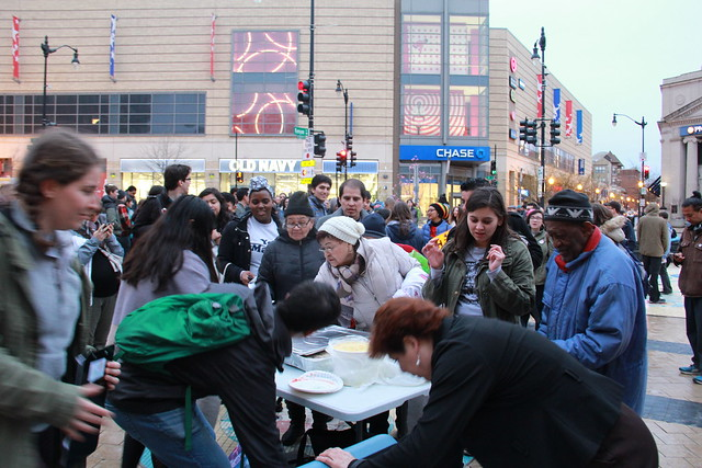 Photo of people lining up at a table where plates and food are availabe.
