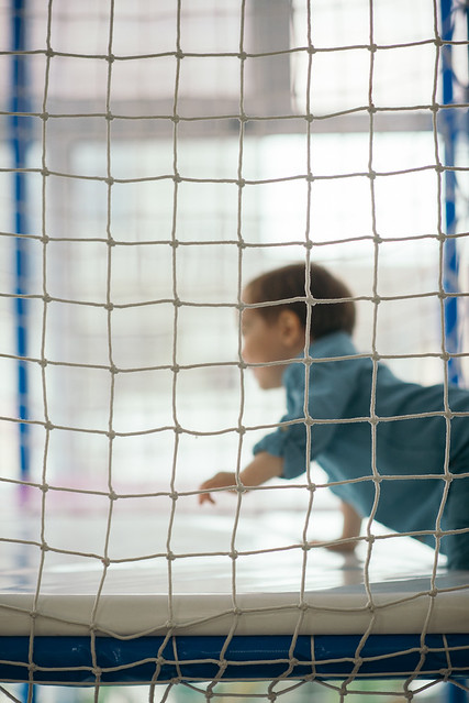 A boy playing in a playroom behind a safety net