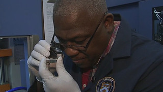 West Point Mint employee examining coin
