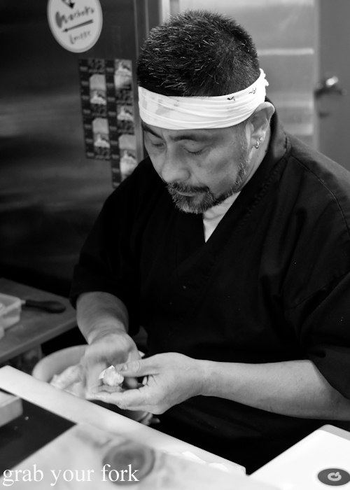 Chef Kazu Nakatani gently pressing school prawns onto sushi rice for his omakase sushi menu at Osaka Bar in Darlinghurst Sydney