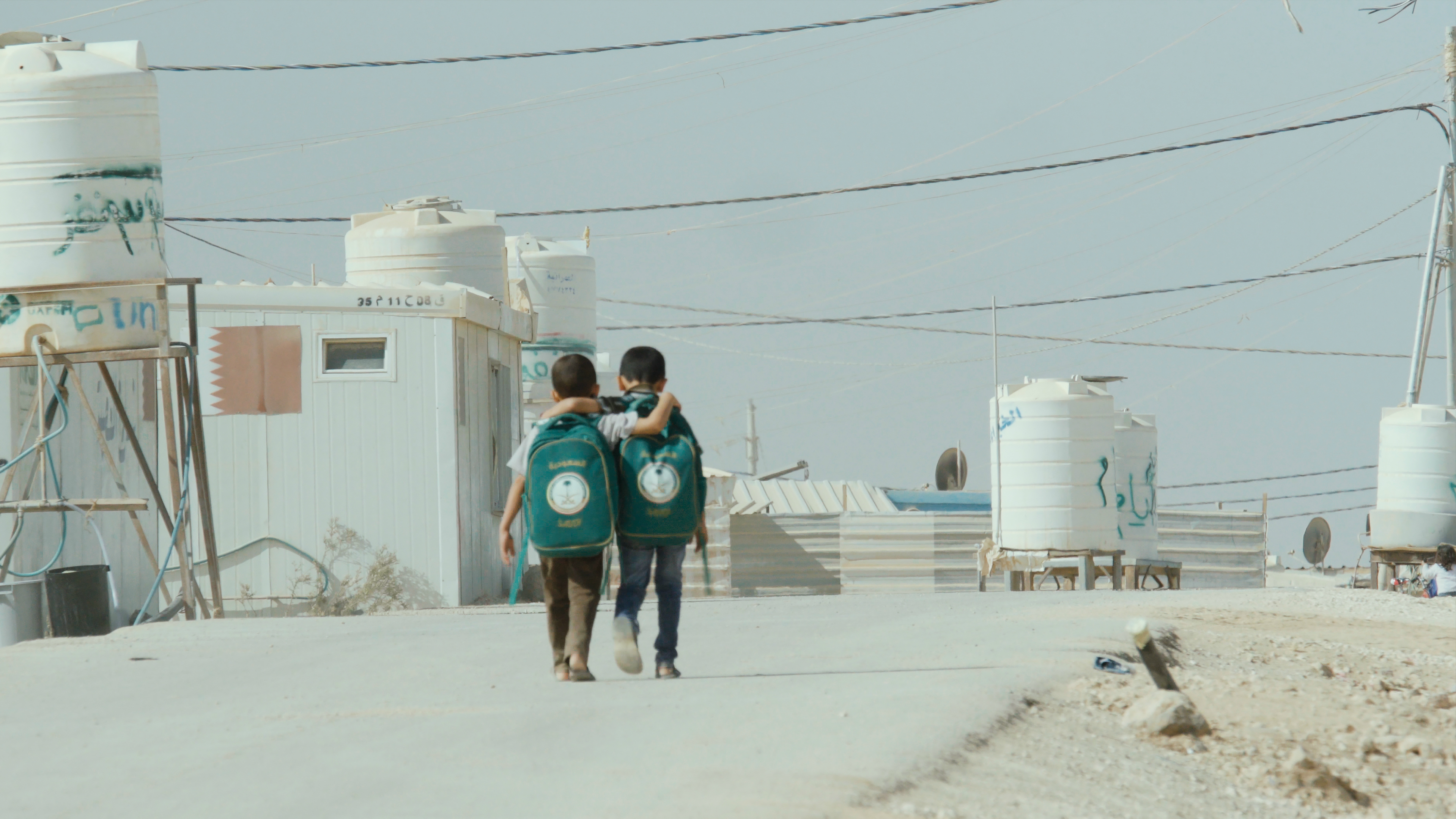 Two boys walking to/from school in a refugee camp