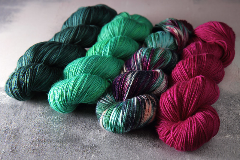 Hand dyed yarn skeins arranged in a fade from sea green to magenta