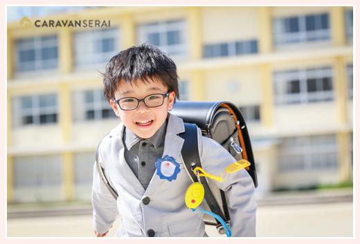 小学校校舎を背景に走る新一年生の男の子