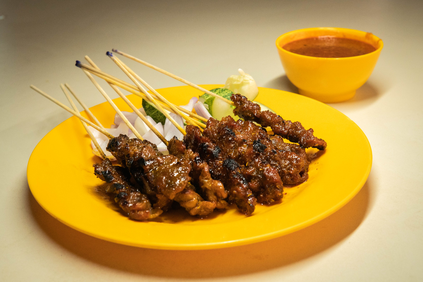 A plate with ten skewers of satay