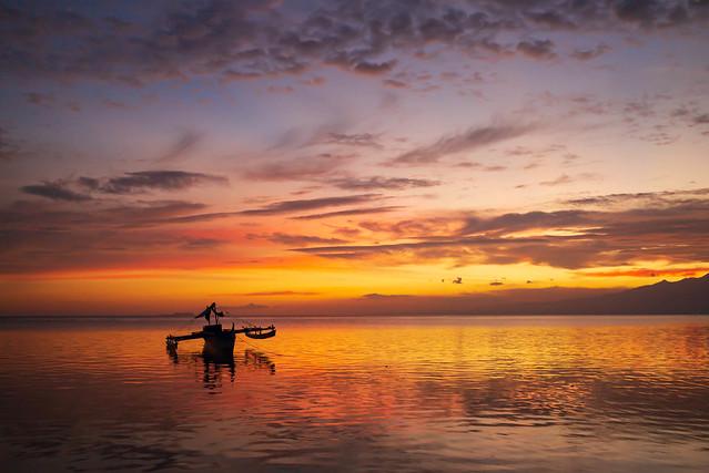 Coucher de Soleil éclairant un bateaux sur la plage de Paliton avec Cebu en arrière plan