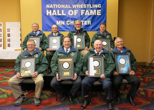 National Wrestling Hall of Fame Minnesota Chapter 2019 Class. Front (L-R): Jim Bartels, Paul Marquart, Paul Bengston, and Lyle Freudenberg. Back (L-R): Randy Zimmer, Paul Cyr, Neal Skaar, and Randy Baker. 190427AJF0818
