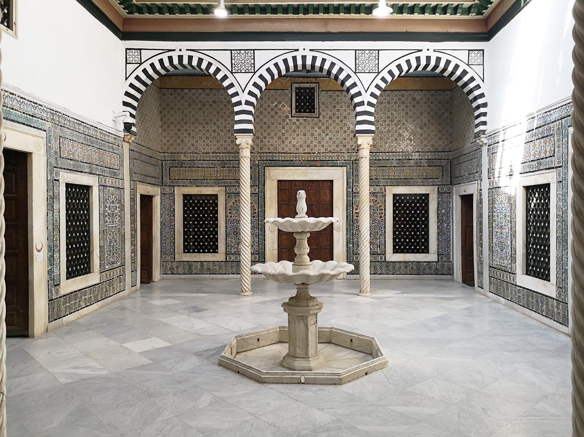 Patio interior fuente tres arcos y paredes de azulejo Museo Nacional del Bardo Tunez