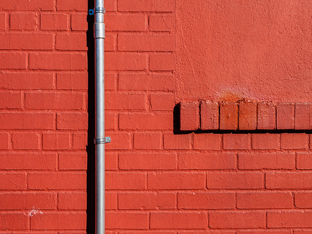 Pipe on a red brick wall