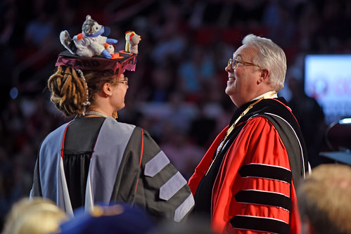 Chancellor Randy Woodson (right) reacts to a College of Veterinary Medicine graduate's mortar board decor.