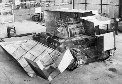 Sunshield' split cover, one half on, one half off a Matilda tank in the workshops at Middle East Command Camouflage Development and Training Centre, Helwan, Egypt, 1941