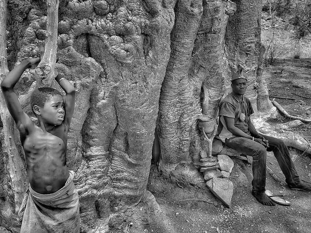 Fotografía en blanco y negro de niña y hombre tamberma (somba) en un baobab sagrado del valle de Koutamakou (Togo)