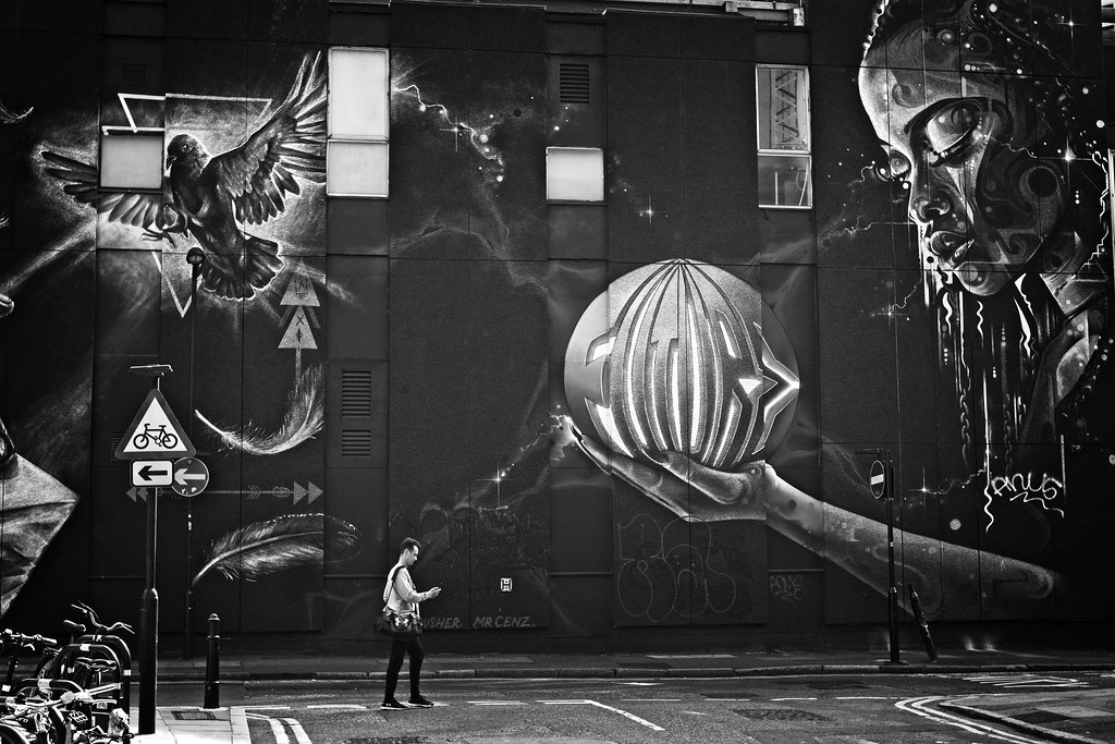 A man engrossed in his smartphone walks past, but doesn't see, street art of a woman looking at a crystal ball, with a caption that reads 'Future'