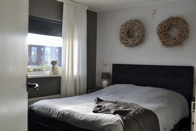 Zwart bed ram vensterbank kransen muur