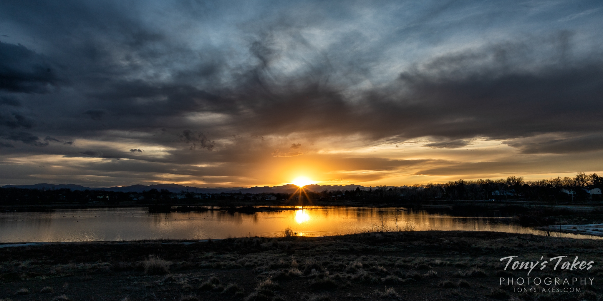 The sun sets behind the Rocky Mountains as seen from Thornton, Colorado. (© Tony's Takes)