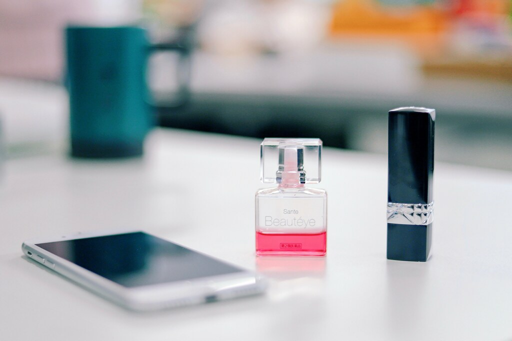 smartphone on a table next to fragrance bottle and black lipstick bottle  - Credit to https://myfriendscoffee.com/