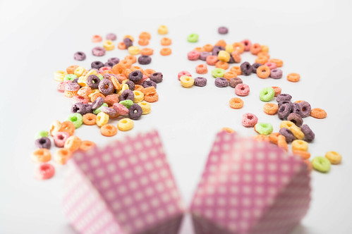 Fruit loops and pink cardboard cups on a white surface | by wuestenigel