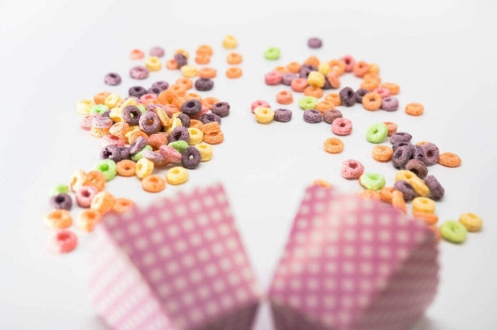Fruit loops and pink cardboard cups on a white surface
