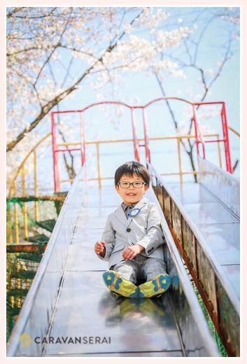 青空と桜をバックに滑り台をすべる新一年生の男の子