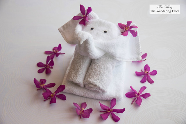 An adorable elephant-shaped towel on my bed with fresh orchids