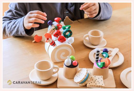 木のおもちゃ ミラン ロールケーキでままごと遊びをする女の子
