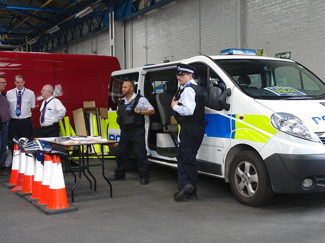 POLICE VEHICLE AND PEOPLE STANDING IN AN EAST LONDON BOROUGH SUBURB STREET BUS GARAGE OR DEPOT  WITH POLICE HATS AND OTHER ITEMS ON DISPLAY. AT THIS BUS OPEN DAY VENUE ENGLAND DSC01674