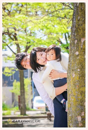 公園で木から顔を出す親子 ファミリーフォト撮影
