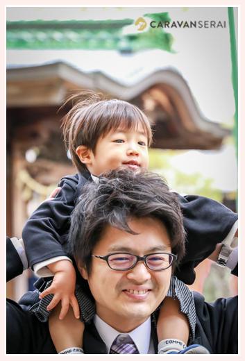 初宮参りで神社 息子を肩車するパパ