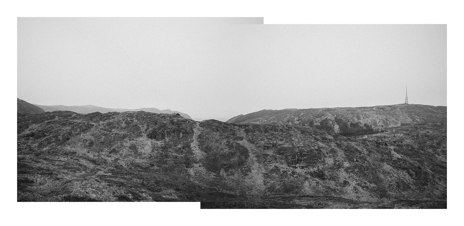 A diptych, black and white, panorama of mountain landscape with two radio masts.