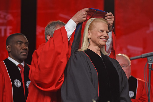 Board of Trustees chair Jimmy Clark hoods honorary doctorate recipient Ginni Rometty.