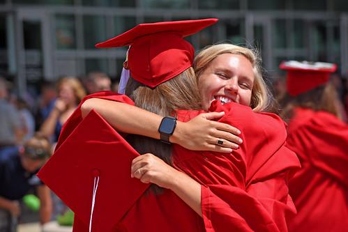Graduates celebrate their success with a hug.