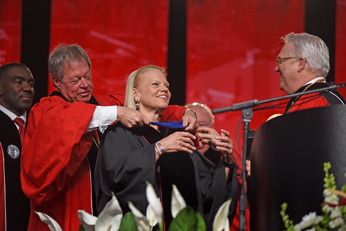 Board of Trustees chair Jimmy Clark (left) hoods honorary doctorate recipient Ginni Rometty as Chancellor Randy Woodson watches.