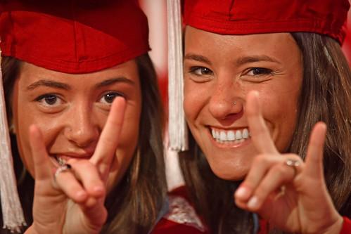 Pair of happy graduates flash their Wuf hands.