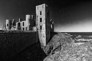 Slains Castle sits moodily in high contrast sunshine, fine art black & white. New Slains Castle, Cruden Bay, Aberdeenshire, Scotland