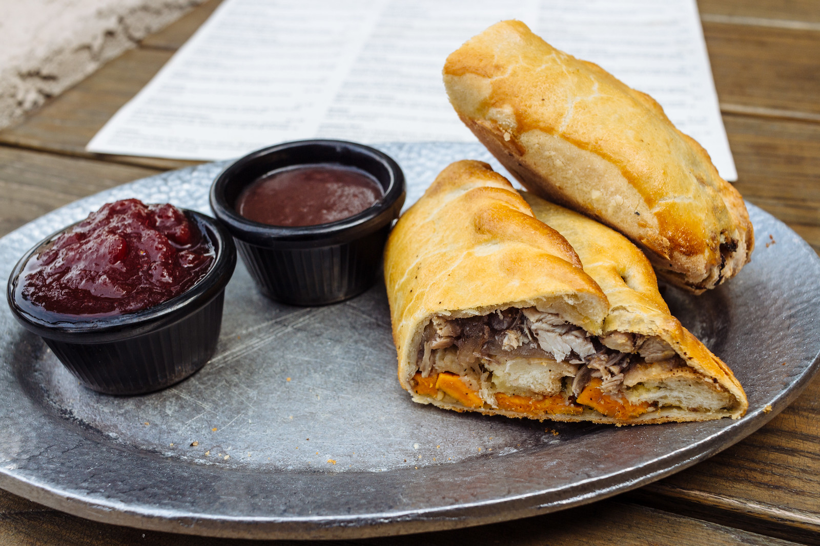 A meat pie of turkey and sweet potatoes sliced in half with containers of cranberry sauce and gravy