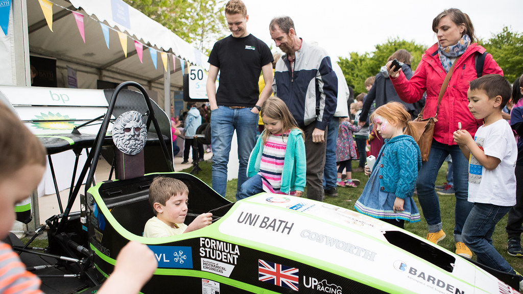 A family with young children gathered round a Formula 1 race car talking to an male engineer with a child seated in the car.