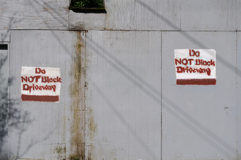 Two signs painted on an old garage say Do Not Block Driveway in the Irvington neighborhood of Portland, Oregon in April 2017