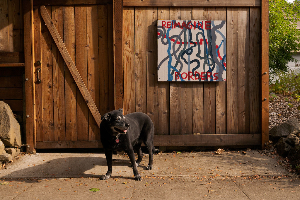 Our dog Ellie stands in front of a fence with a painting that says 'Reimagine Borders' in the Irvington neighborhood of Portland, Oregon in August 2017