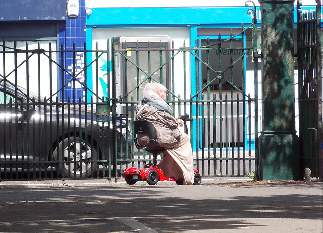 LADY SITTING ON A MOBILITY SCOOTER ENJOYING AN EAST LONDON BOROUGH SUBURB STREET PARK ON A WARM SUNNY DAY ENGLAND DSCN0072 c