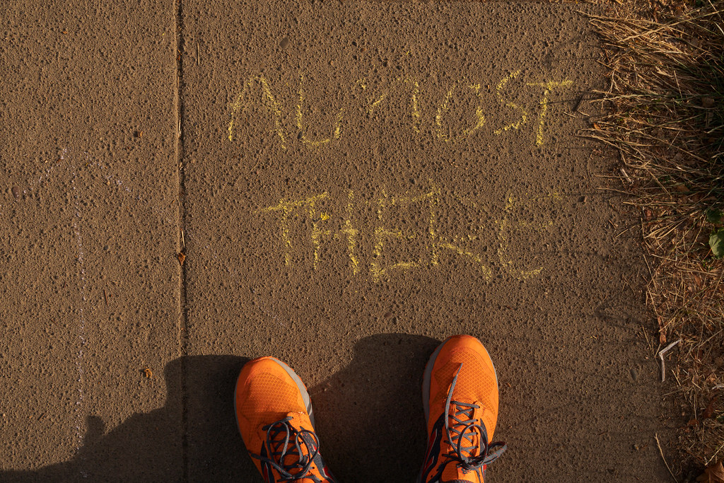The words 'Almost There' are written in chalk on the sidewalk beside my orange shoes as I walked on the sidewalk in the Irvington neighborhood of Portland, Oregon in August 2017