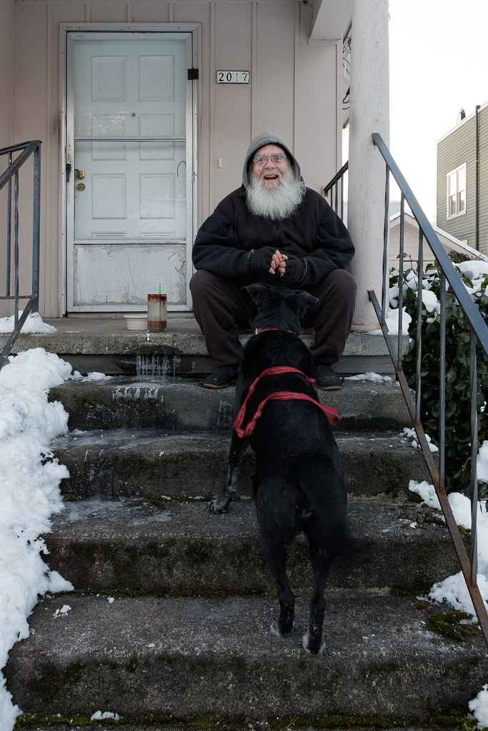 A neighbor laughs while feeding our dog Ellie treats from the steps of his house on a snowy day in the Irvington neighborhood of Portland, Oregon in January 2017