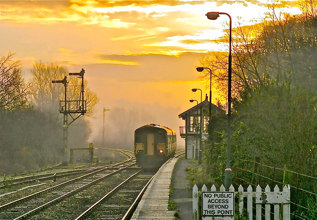 Arriving in a spectacular sunrise an Anglia Railways class 150 passes Brundall Junction signalbox on route to Norwich November 2002