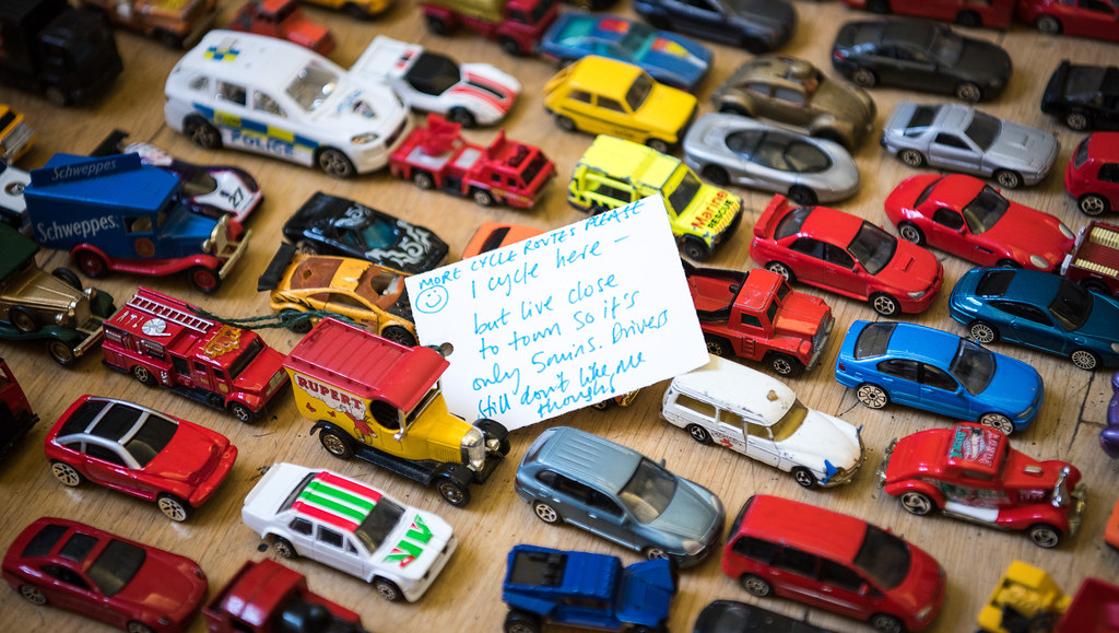 A display of 100 toy cars lined up on a table