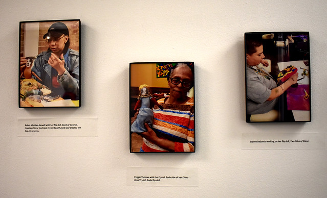Photo of three framed photographs of people participating in doll making, mounted on a gallery wall.