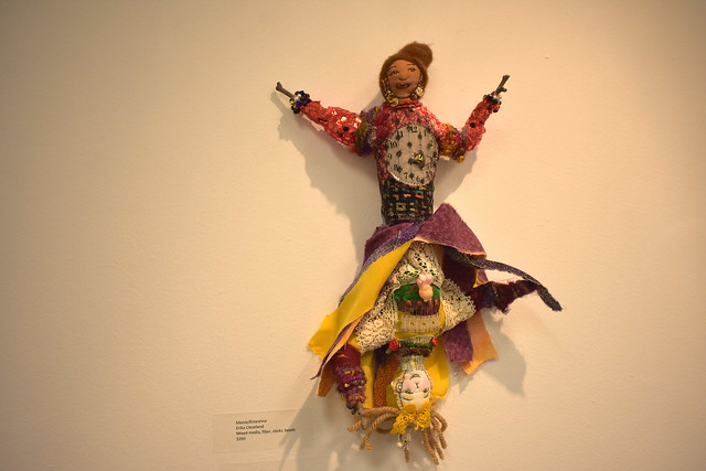 Photo of a cloth doll mounted on a gallery wall showing a head and pair of arms at either end with a dress that could flip to cover either of them.